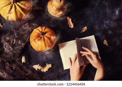 top view of woman reading book surrounded by halloween pumpkins with smoke and witch hat