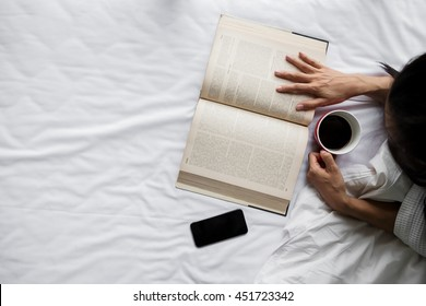 Top view of woman relax on white bed with drinking coffee and read a text book.
