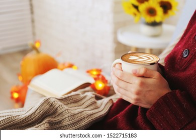 Top view of woman relaxing on couch at home, drinking latte. Cozy evening at home. Young woman enjoying alone time, sitting on sofa covered with soft blanket. Close up, copy space.