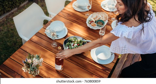 Top view of woman setting champagne bottle on wooden table for housewarming party. Female preparing a dining table outdoors with food and drink.
