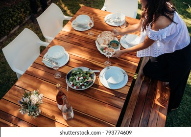 Top view of woman setting food on wooden table for housewarming party. Female preparing a table outdoors with food and drink.