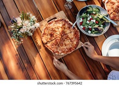 Top view of woman setting pizza and salad on wooden table for housewarming party. Female preparing a dining table outdoors with food for dinner.