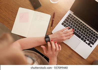 Top view of woman sitting at her desk and using smartwatch. Laptop and diary on the table.