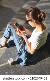 top view of a woman sitting on tne street with a phone in hands and cup of coffee