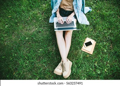 Top view of woman sitting in park on the green grass with laptop, notebook and smartphone, hands on keyboard. Computer screen mockup. Student studying outdoors. Copy space for text
