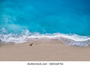 Top view of a woman sunbathing lying down on the tropical beach summer travel holidays drone shot