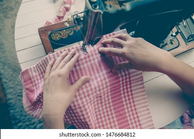 Top view of woman tailor working with old vintage sewing machine at home