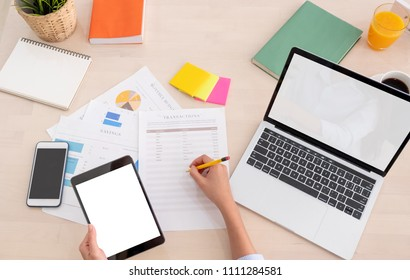 top view woman use tablet and writing on paper sheet with laptop working online on table at home.mock up template device screen.Digital lifestyle concept.clipping path screen