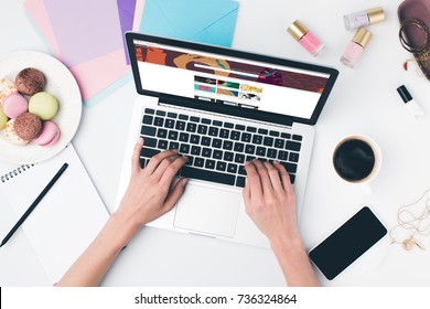 top view of woman using laptop at modern workplace with shutterstock website