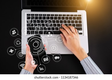 Top view woman using smart phone for mobile payments online shopping,omni channel,sitting on black table,virtual icons graphics interface screen in morning light