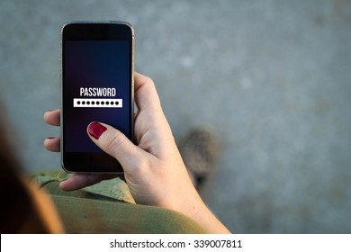 Top view of woman walking in the street using her mobile phone with password screen with copyspace. All screen graphics are made up.