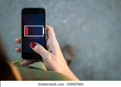 Top view of woman walking in the street using her mobile phone with low battery on screen with copyspace. All screen graphics are made up.