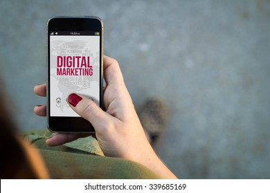 Top view of woman walking in the street using her mobile phone with digital marketing on screen. All screen graphics are made up.