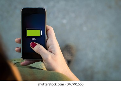 Top view of woman walking in the street using her mobile phone with full battery on screen with copyspace. All screen graphics are made up.