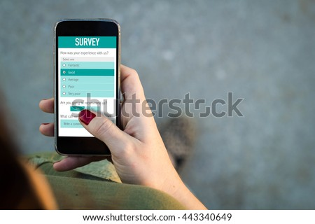 Top view of woman walking in the street using her mobile phone with online customer service satisfaction survey. All screen graphics are made up.