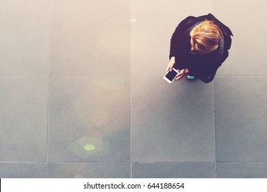 Top view of a woman is watching video in internet on cell telephone, while is standing on background with copy space. Blonde female student with a rucksack on her back is chatting on smart phone