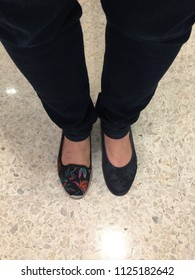 Top view of a woman wearing a pair of black trousers and mismatched casual shoes and standing on a floor.