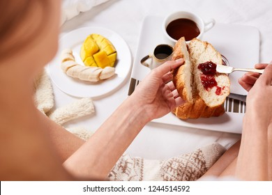 top view of a woman in white t-shit and wool knitted socks sitting on the bed with breakfast and spreads croissant with jam. a plate with croissants, jam and fruit and cup of coffee for breakfast in