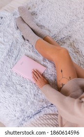 Top view of woman in wool sock and sweater with pink notebook sign 2021, large tattoo on hip. Female sit on bed at home in bedroom.