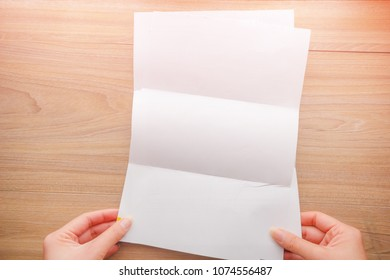 Top view, Woman's hand holds white paper, documents paper and space for text on wooden background.