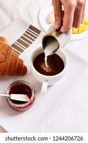 top view of a woman's hand pouring milk in coffee. a plate with croissants, jam and fruit and cup of coffee for breakfast in bed