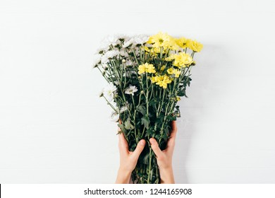 Top view woman's hands holding bouquet of daisy flowers of white and yellow colors, flat lay floral composition on wooden table.