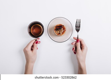 Top view of a woman's hands holding a cup of tea and fork, on the plate is a sweet cake