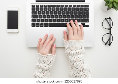 Top view of woman's hands typing on laptop keypad placed on white office desktop with blank smartphone, glasses and decorative plant. Mock up minimal flat lay