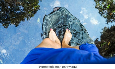 Top view of womans legs standing barefoot on a black rock in the river sourrounded by water