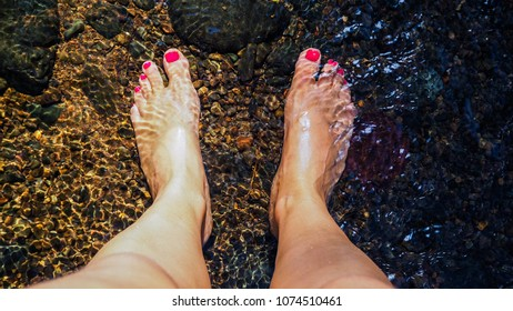 Top view of womans legs standing barefoot in the clear cold water of river with polished pink nails for refreshing