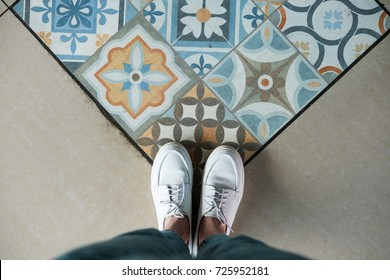 Top view of woman's legs standing on the floor with mosaic tile