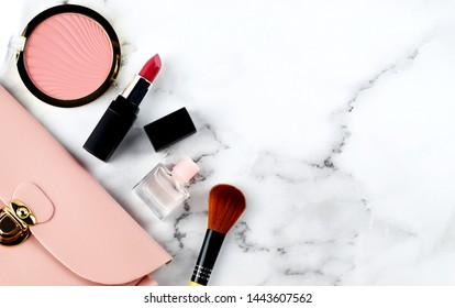 Top view of woman's light pink cosmetics bag on white marble background with pink cheek blush, pink lipsticks, pink mini perfume bottle and a makeup brush, beauty care concept, copy space for text