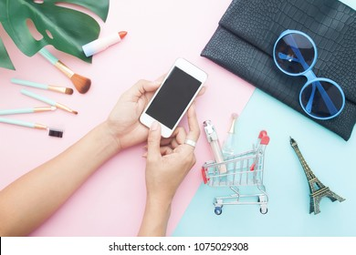 Top view of woman's using mobile phone for online shopping with beauty items on pastel color background, Online shopping