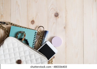 Top view of Women bag and lady stuff with copyspace on wooden background