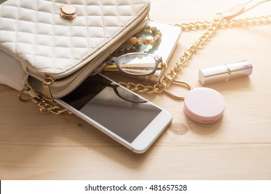Top view of Women bag and lady stuff with copyspace on wooden background, vigtage effect photo