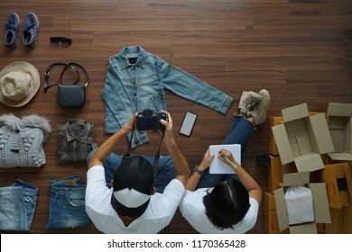 Top view women and men selling online start up small business owner working taking photo to shirts with digital camera for post to sell Online on the internet