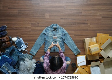 Top view of women take a photo jeans jecket with smart phone from home on wooden floor with postal parcel, Selling online ideas concept