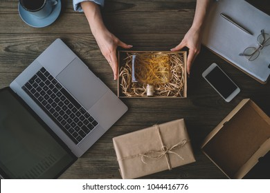 Top view of women working laptop computer at home on wooden desk with postal parcel. Selling online ideas concept. Start up small business entrepreneur woman working on line packaging box and delivery