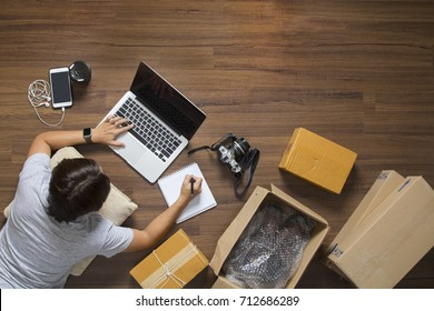 Top view of women working laptop computer from home on wooden floor with postal parcel, Selling online ideas concept