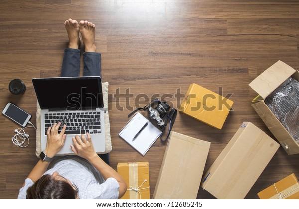 Draufsicht von Frauen, die Laptop-Computer von zu Hause aus auf Holzboden mit Postpaket, Verkauf von Online-Ideen Konzept