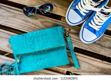 Top view of women's accessories, a blue bag, high-heeled shoes and sunglasses on a wooden background, a modern and fashionable concept.
