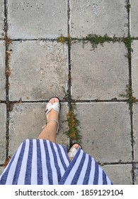Top view of women's fashionable legs in trendy white jeans in stylish red-black summer shoes on a stone tile on the street. women's feet in sandals walk on street tiles