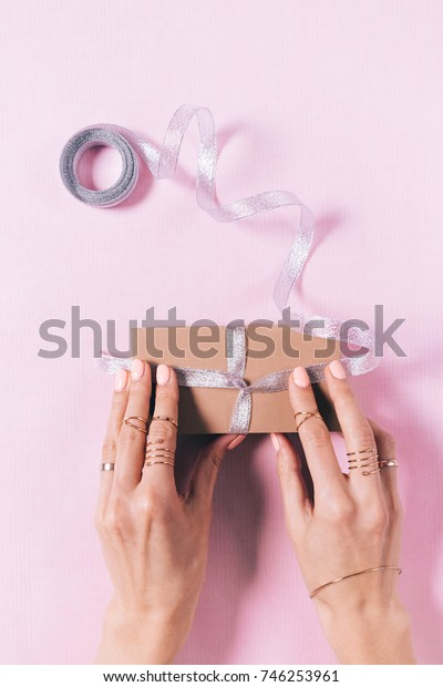 Top view of women's hands tying a bow on a gift box