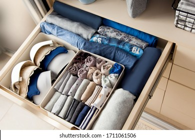 Top view of womens things and accessories of blue color are in the drawer of the wardrobe closet during tidying by the lady fly system. Convenient and intelligent storage concept