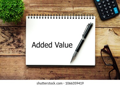 Top view wood desktop background with Notebook write text Added Value for business and finance concept.