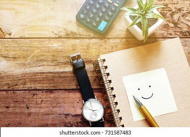 Top view wood desktop have watch,calculator,pot plant,pen,notebook and note drawing smile face.Have copy space.For happy work place,work life balance concept.