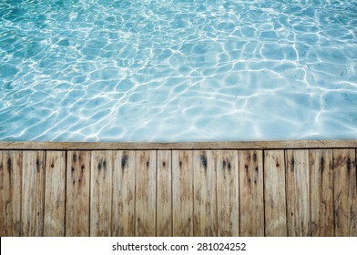 Top view of wood floor or terrace beside the blue crystal clear water. There are little fishes in water.