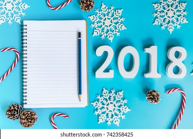 top view wood number 2018, notebook and christmas decoration for new year on blue pastel color.