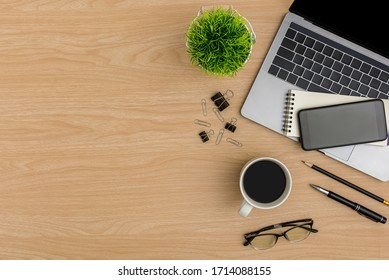 Draufsicht Wood Bürotisch. Flaches WorkSpace mit Brillen, Kaffeetasse, Baumtopf, Smartphone, Maus-Computer, Papierklammer, Notebook, Bleistift, Bürobedarf auf Holzhintergrund
