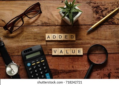 "Top view wood text ""Added value"" with brown glasses,calculator,gold pen,black watch,magnifying glass and white pot plant.For Thinking Business Plan concept.Have copy space"